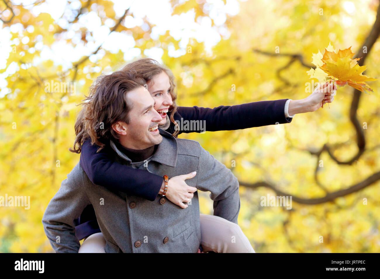 El amor, las relaciones, la temporada y el concepto de pueblo - feliz pareja joven divirtiéndose en otoño park piggyback ride Imagen De Stock
