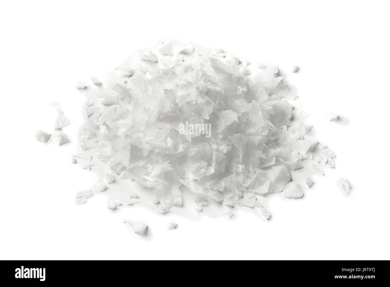 Montón de escamas de sal sobre fondo blanco. Imagen De Stock
