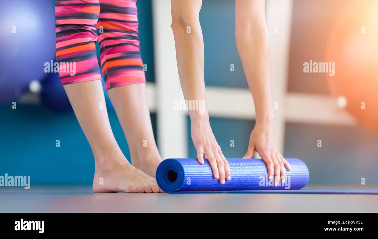 Mujer joven azul plegada o gimnasio yoga mat después de trabajar. Vida sana, manteniendo el concepto apto. Foto de stock