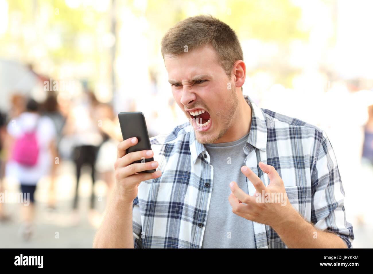 El hombre enojado mantiene bloqueado el teléfono móvil en la calle Imagen De Stock