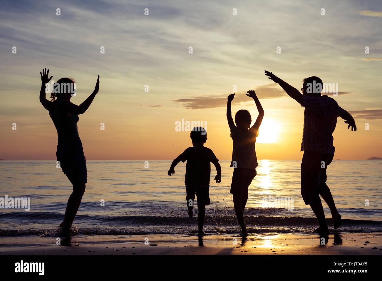 Silueta De Familia Feliz Que Jugando En La Playa Al