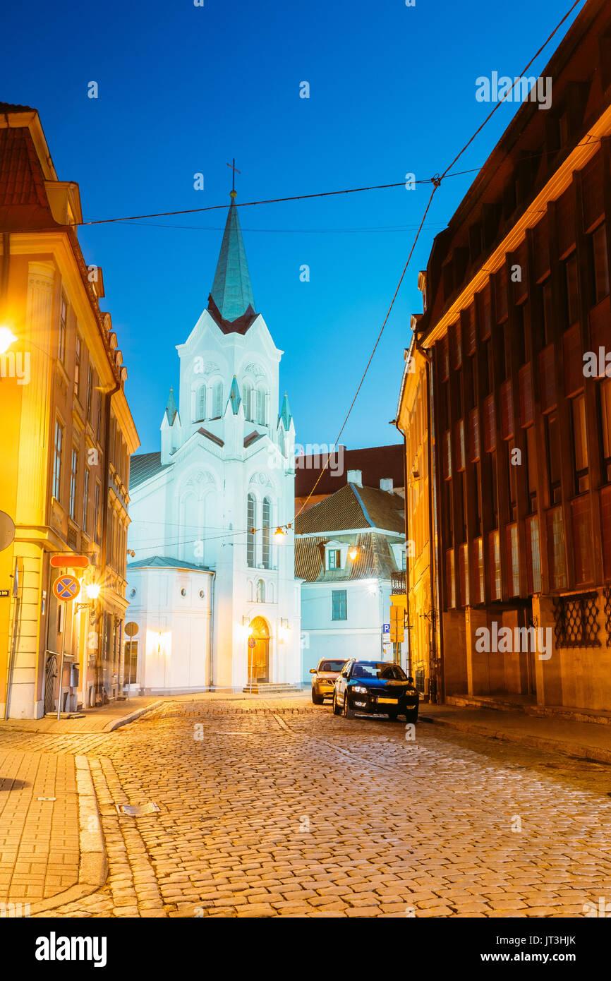Riga, Letonia. Torre blanca con aguja piramidal de Nuestra Señora de los dolores o Virgen de la angustia, la antigua iglesia Iglesia católica sobre la pils Street en la tarde Il Imagen De Stock