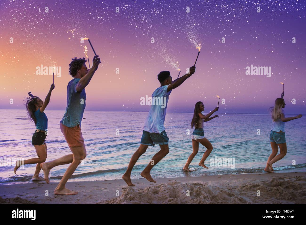 Feliz sonriendo amigos corriendo en la playa con espumosos velas Imagen De Stock