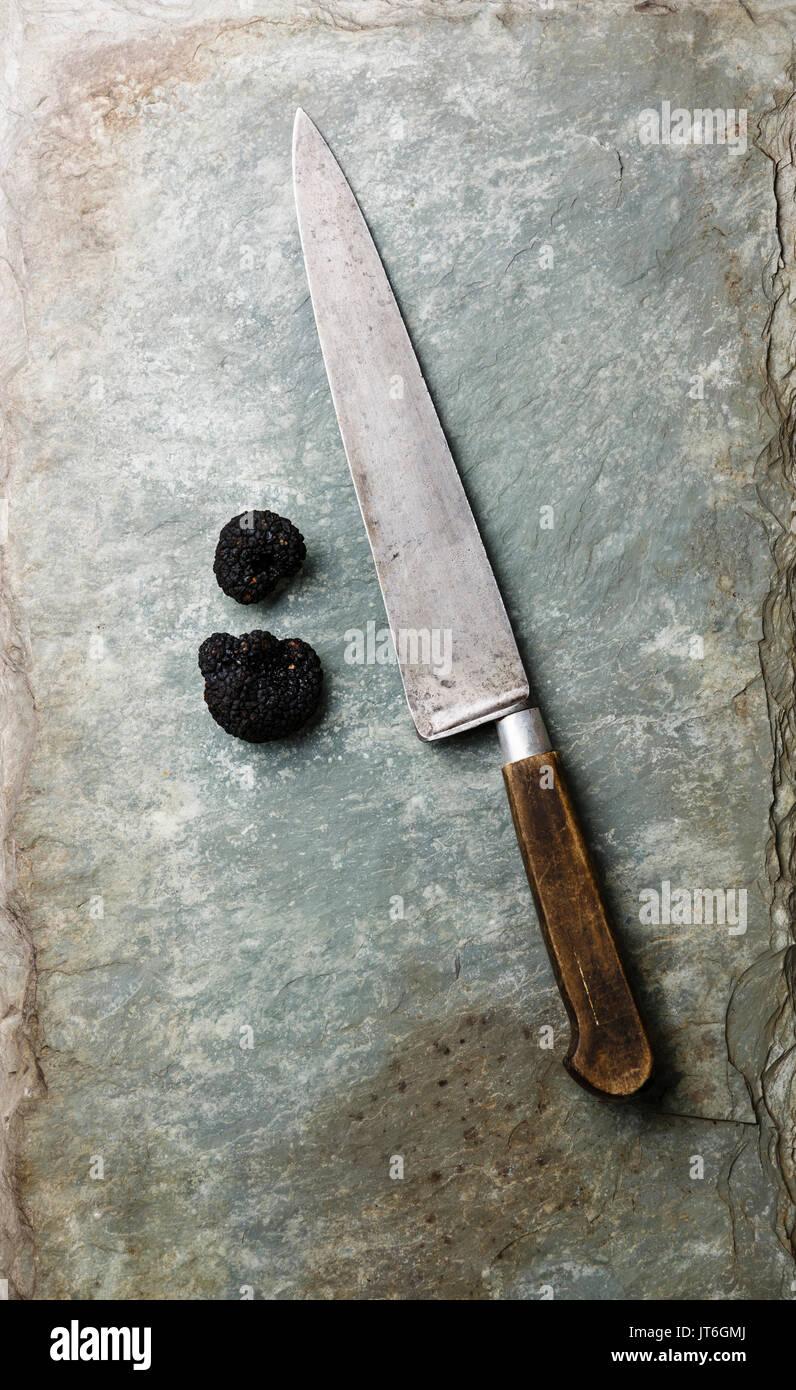 La trufa negra y el cuchillo de cocina en piedra pizarra esquisto antecedentes Foto de stock