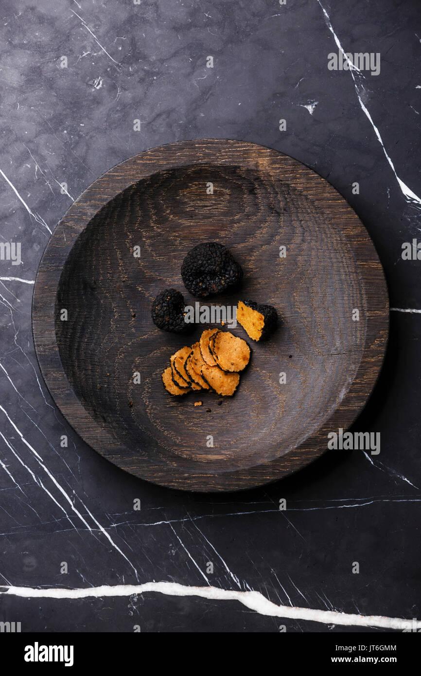 Placa de madera en la trufa negra sobre fondo de mármol oscuro Foto de stock