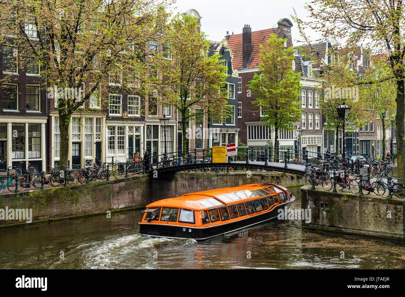 Canal Boat pasando bajo un puente en el Brouwersgracht, Amsterdam, Países Bajos, Europa Foto de stock