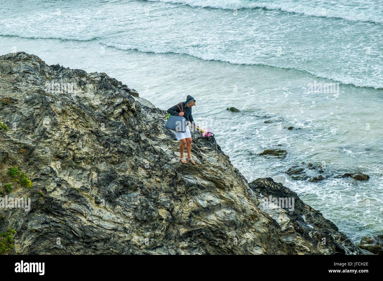 Una mujer subiendo rocas resbalosas en godrevy playa de Cornwall. Imagen De Stock