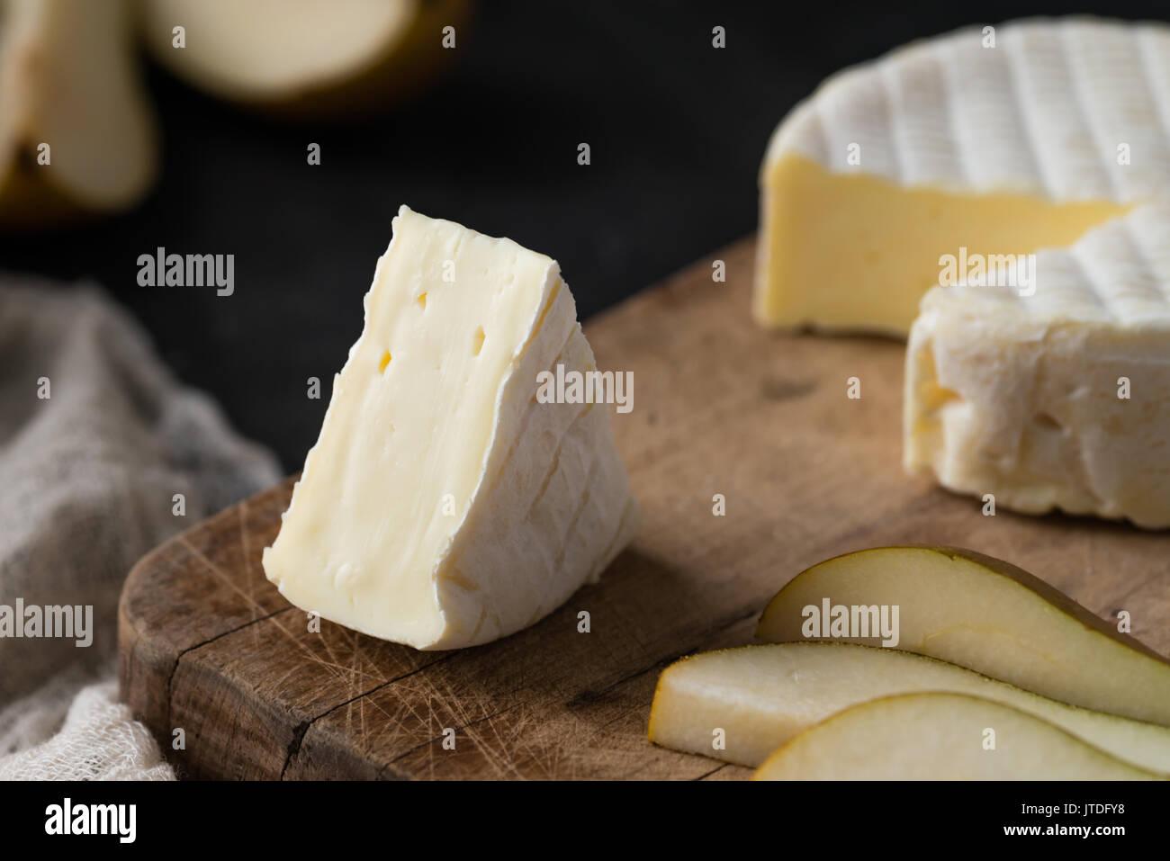 Acercamiento de queso francés de la región de Normandía con pear en rodajas sobre una tabla de madera en el oscuro fondo rústico Imagen De Stock