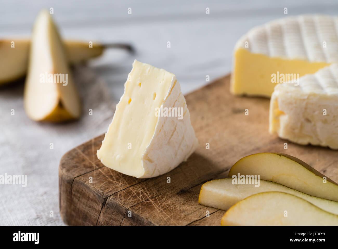 Acercamiento de queso francés de la región de Normandía con pear en rodajas sobre una tabla de madera sobre fondo blanco. Imagen De Stock