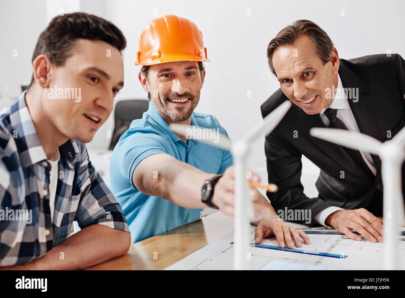 Idea brillante. Cerdas agradables al hombre en un sombrero duro apuntando a una turbina de viento mientras sus colegas sentado junto a él y mirando fijamente al mostrado Imagen De Stock