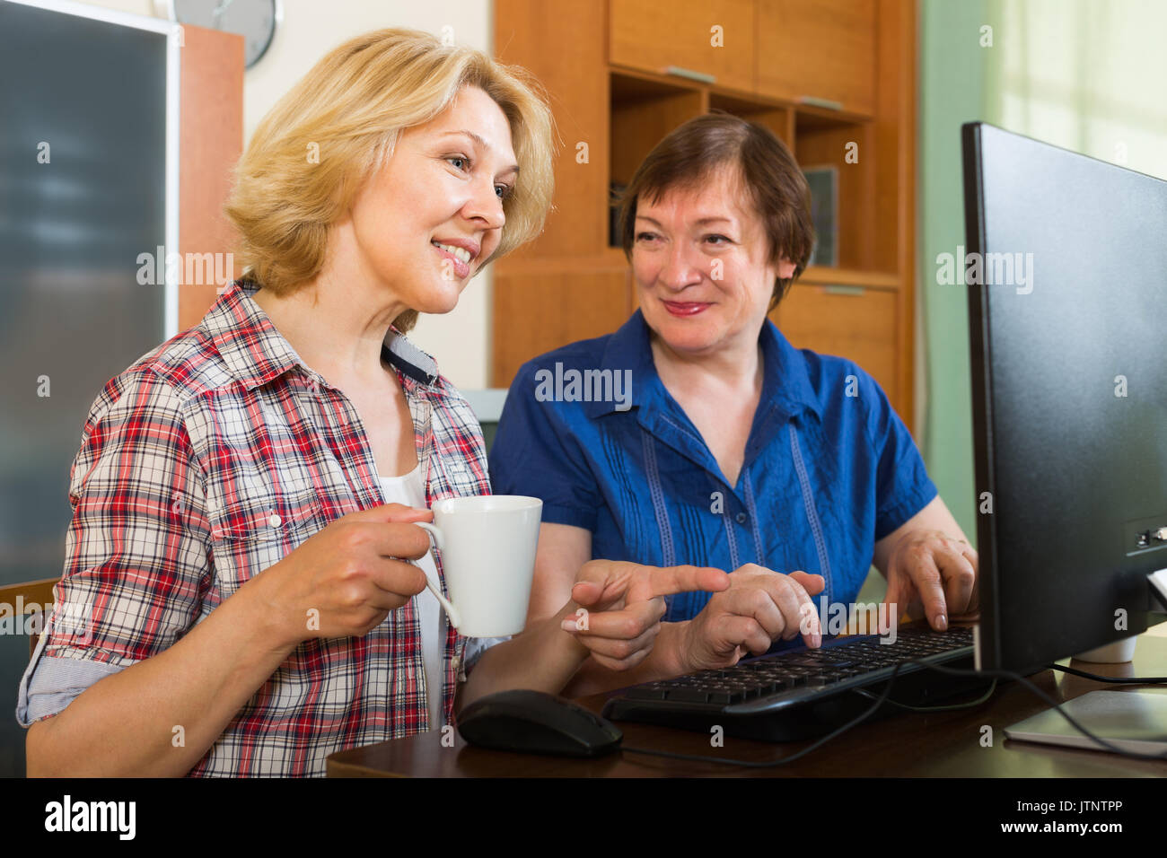 Amigas Maduras dos amigas maduras sonriente bebiendo té y navegación web