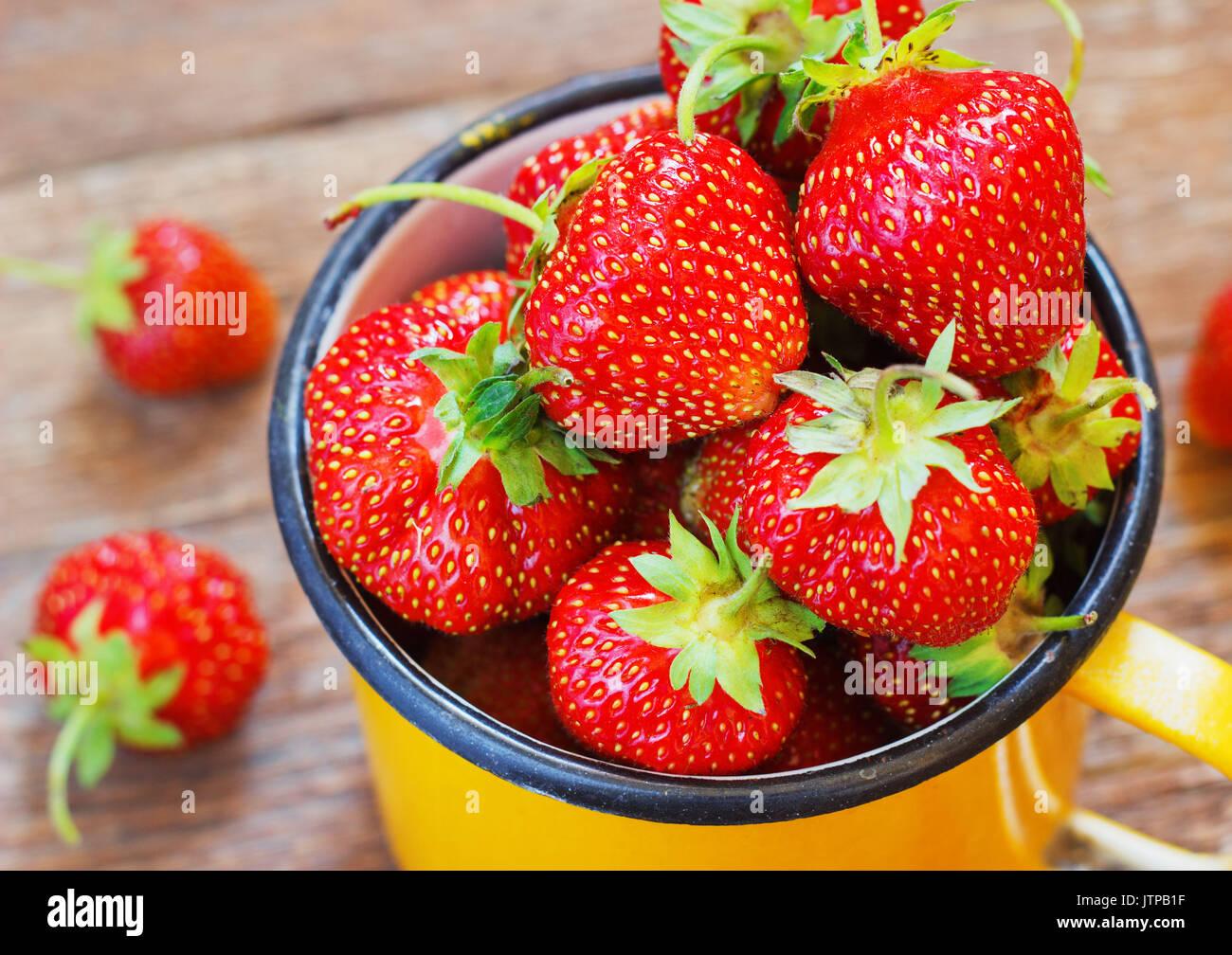 El jardín de la fresa rústico CUP Verano alimentos metal amarillo oscuro fondo Enfoque selectivo Imagen De Stock