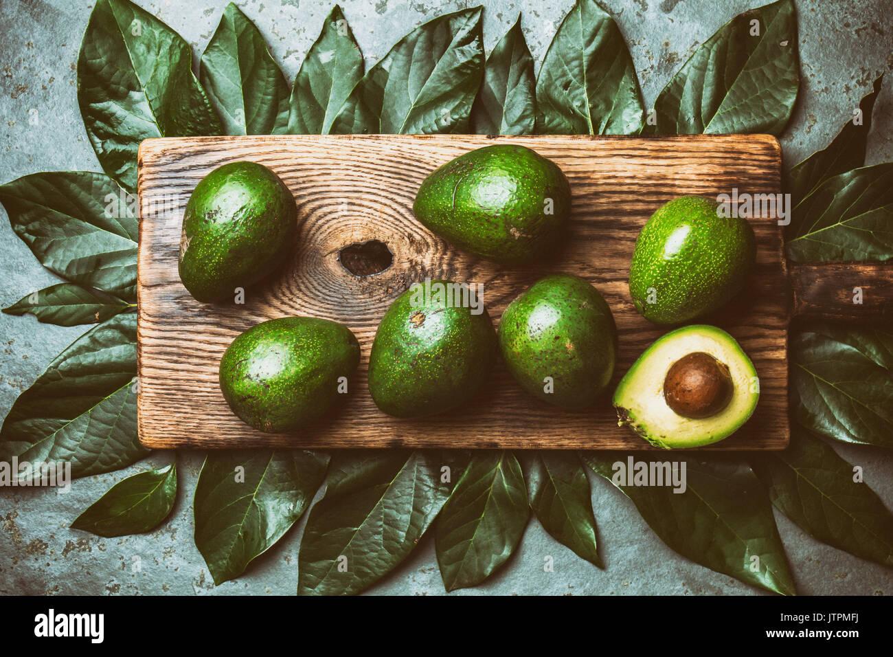 Fondo de alimentos con aguacate fresco, las hojas del árbol de aguacate y junta de corte de madera. Concepto de cosecha, Guacamole ingredientes. Grasa saludable omega 3. La mitad o Imagen De Stock
