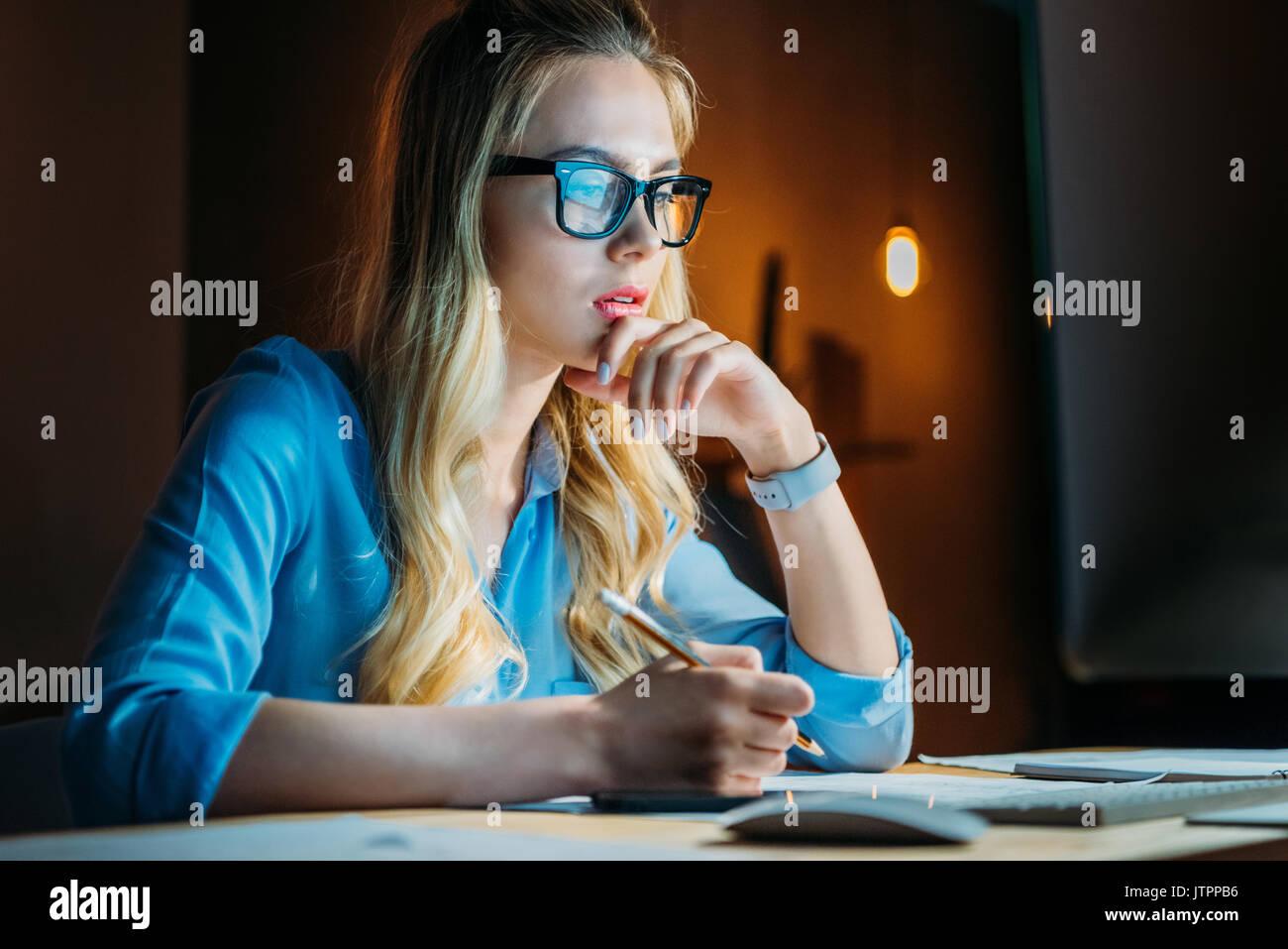 Pensativo joven empresaria en caucásicos anteojos escrito algo con un lápiz y sentarse en el lugar de trabajo Imagen De Stock