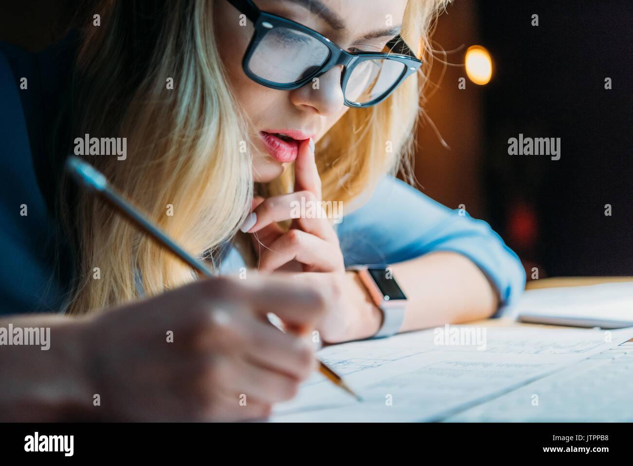 Joven rubia caucásica estudiante en anteojos de pensar y escribir algo con lápiz, estudiando hasta tarde Imagen De Stock