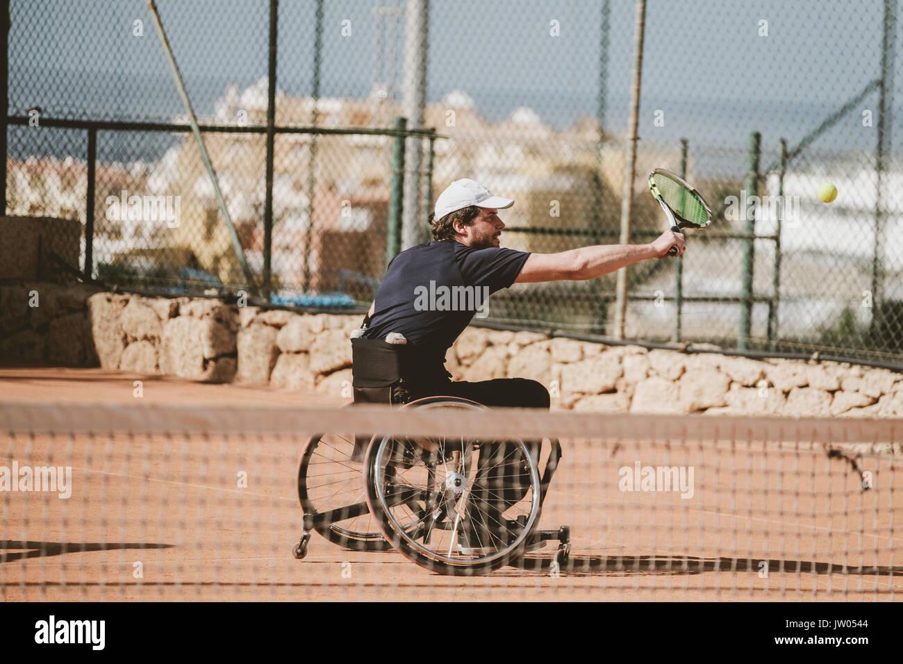 Adulto medio austríaco tenista paralímpico jugando en cancha de tenis Foto de stock