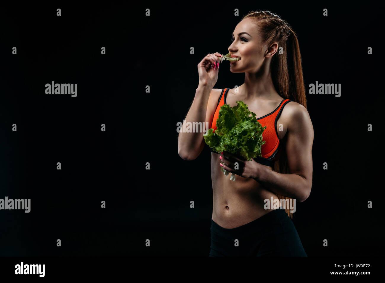 Feliz sportswoman caucásica comer ensalada deja aislado en negro, comer sano concepto Imagen De Stock