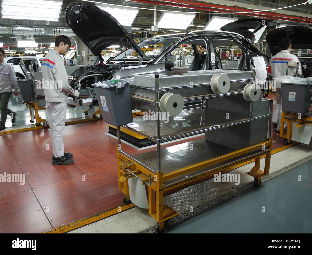 Los trabajadores en la línea de montaje de la planta de producción de automóviles Dongfeng PSA de Chengdu (China) Foto de stock