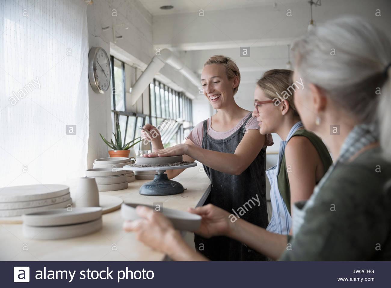 Instructora sonriente explicando el barro a estudiantes en art studio Imagen De Stock