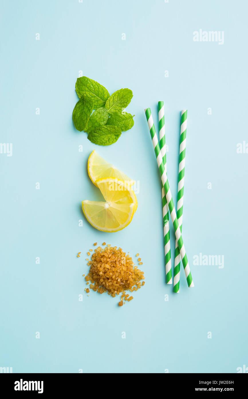 Mojito ingredientes. Limón, menta y azúcar de caña con fondo de color azul. Dulce de azúcar, hojas de menta, limón Foto de stock