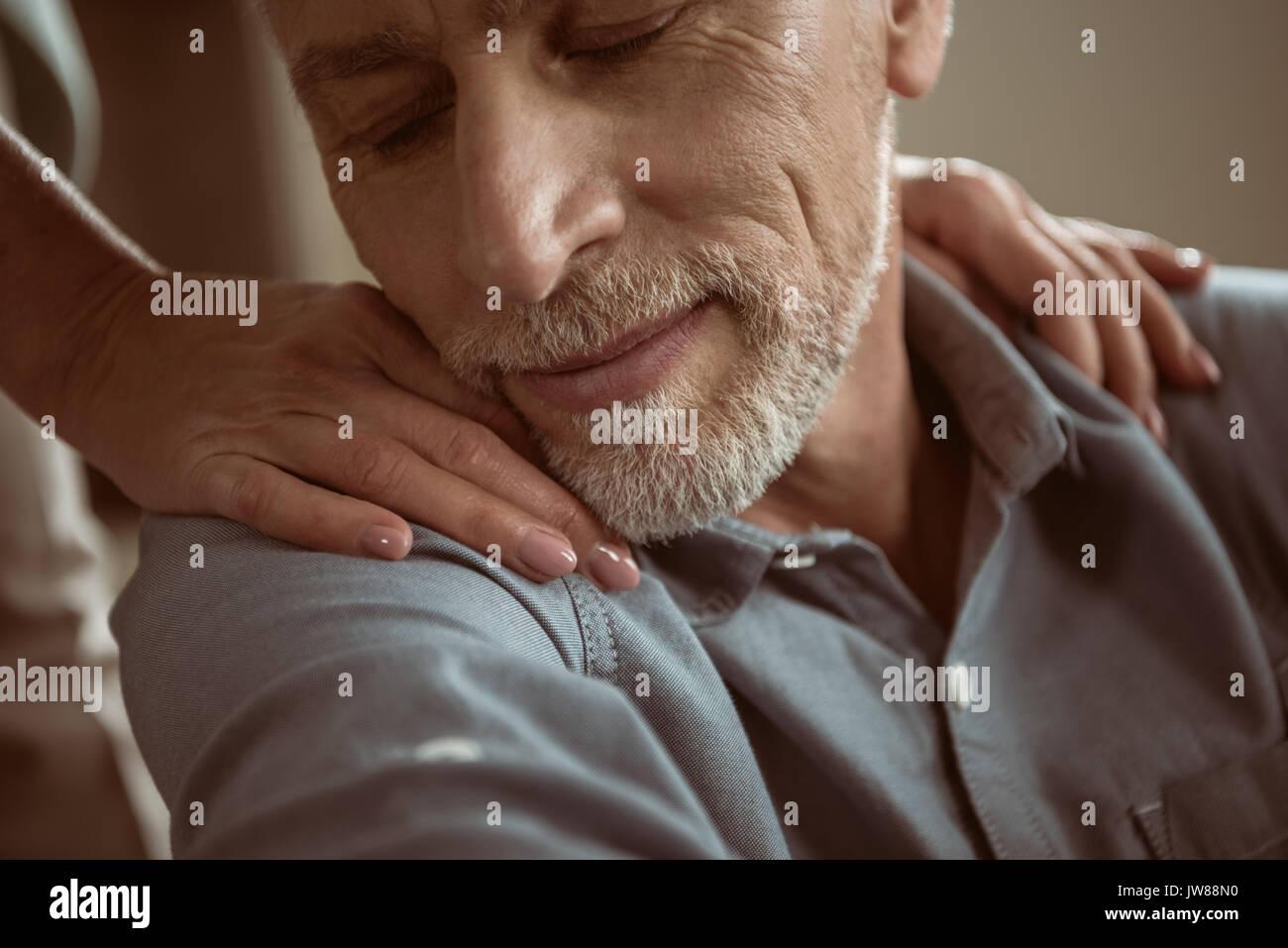 Tierna esposa puso las manos sobre los hombros de su marido con los ojos cerrados Imagen De Stock