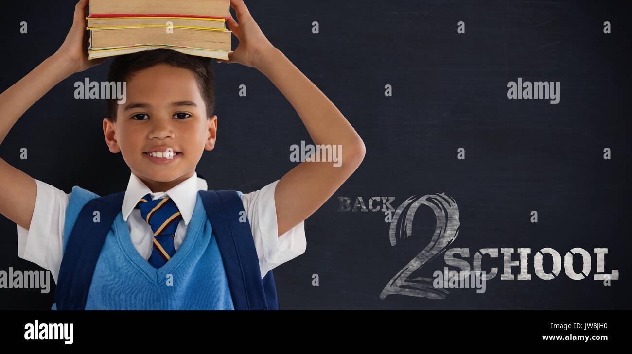 Sonriendo colegial llevar libros en la cabeza sobre fondo blanco contra el fondo negro Foto de stock