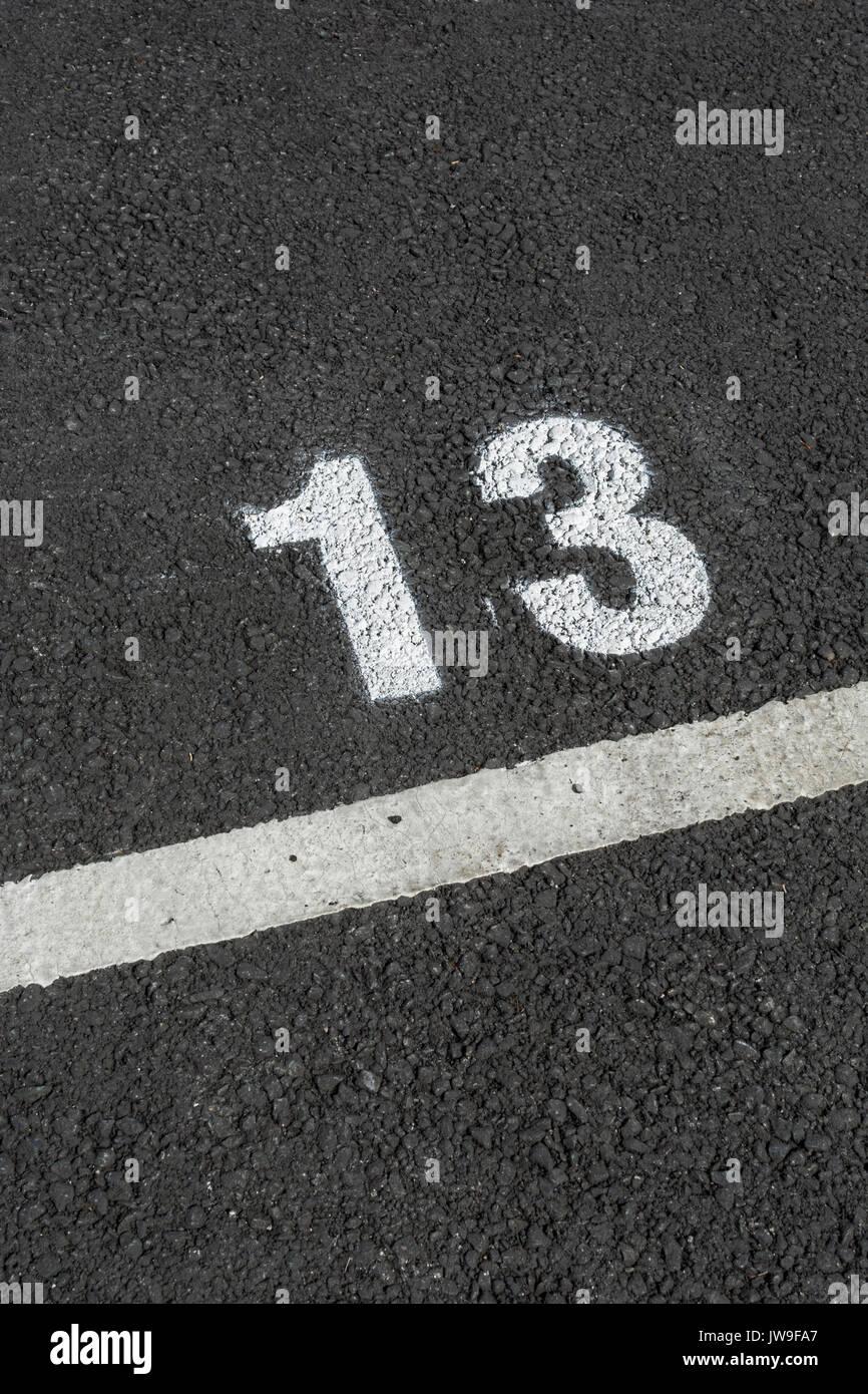 Pintado el número 13 en el asfalto aparcamiento / estacionamiento espacio. Mala suerte y 13 son bien conocidos en la conexión. Número impar. Imagen De Stock