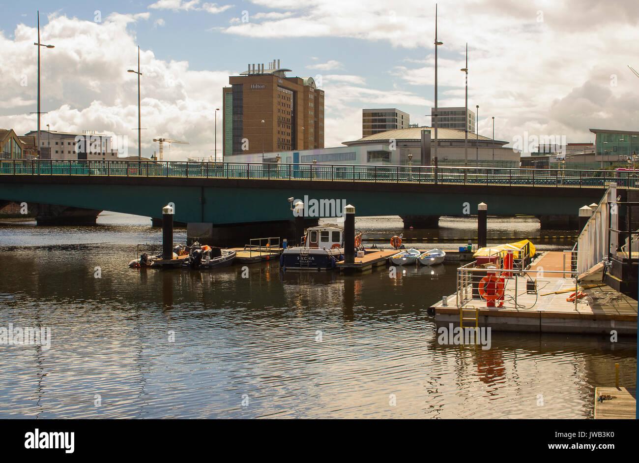 Pequeñas embarcaciones en sus amarras en el Queen Elizabeth 2 puente que cruza el río Lagan en Donegall Quay, en el puerto de Belfast, Irlanda del Norte Imagen De Stock