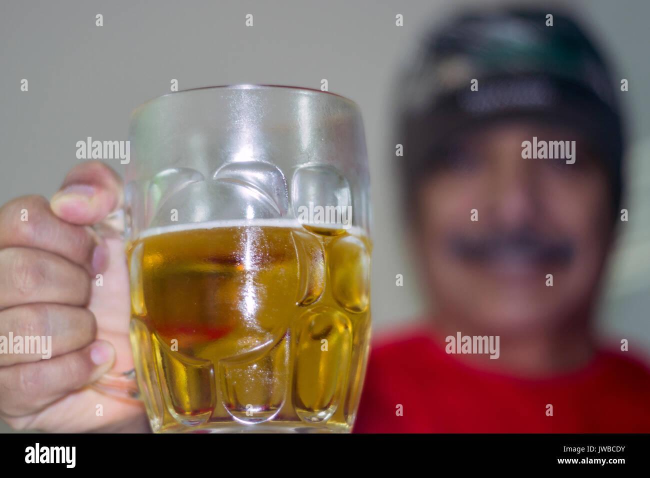 Vaso de cerveza en el cebador plano, un hombre atras desenfocado, empuñando el vaso, saludando y sonriendo, toma horizontal Imagen De Stock