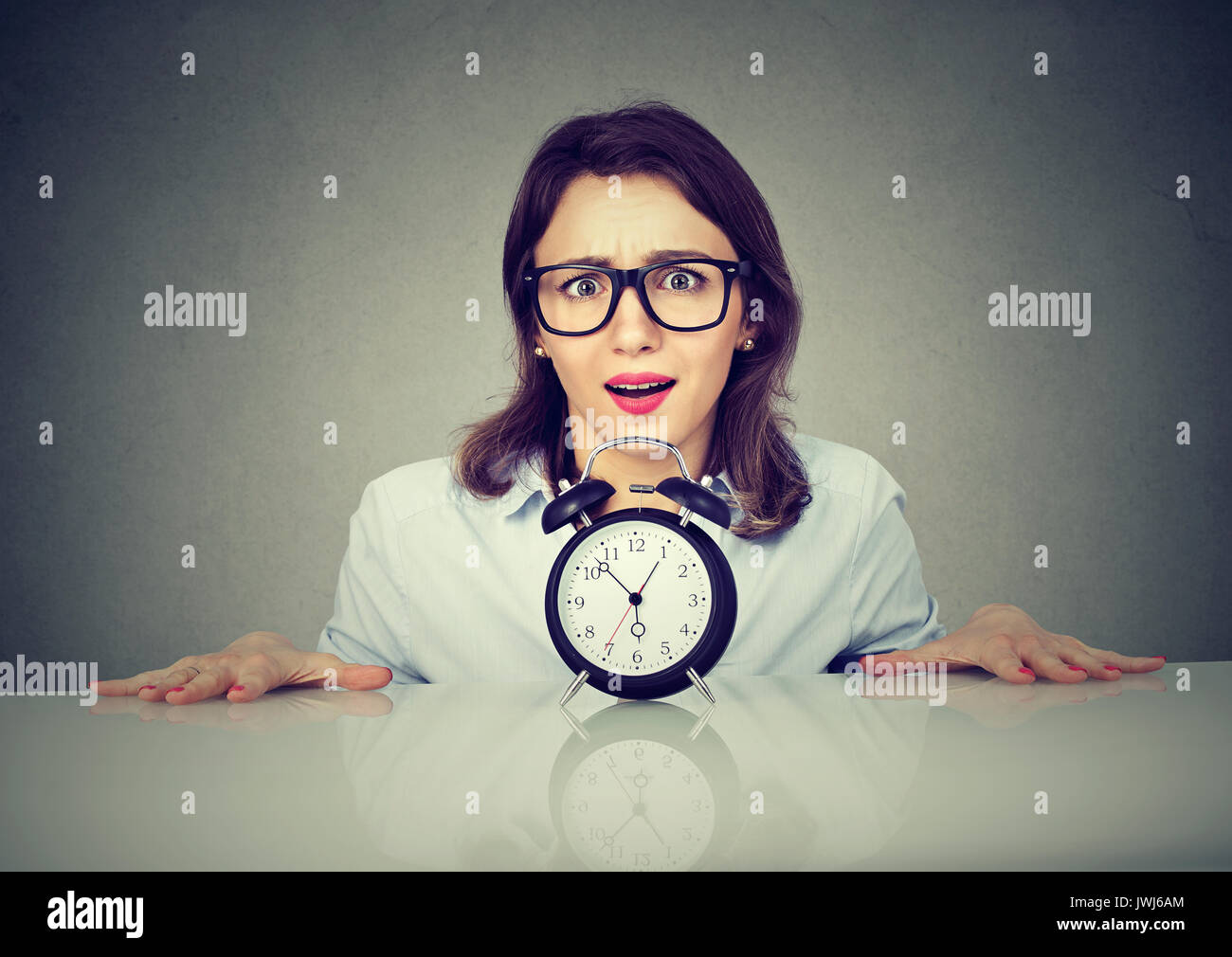 Mujer ansiosa de recogida debajo de la mesa con reloj despertador. La presión del tiempo concepto Imagen De Stock