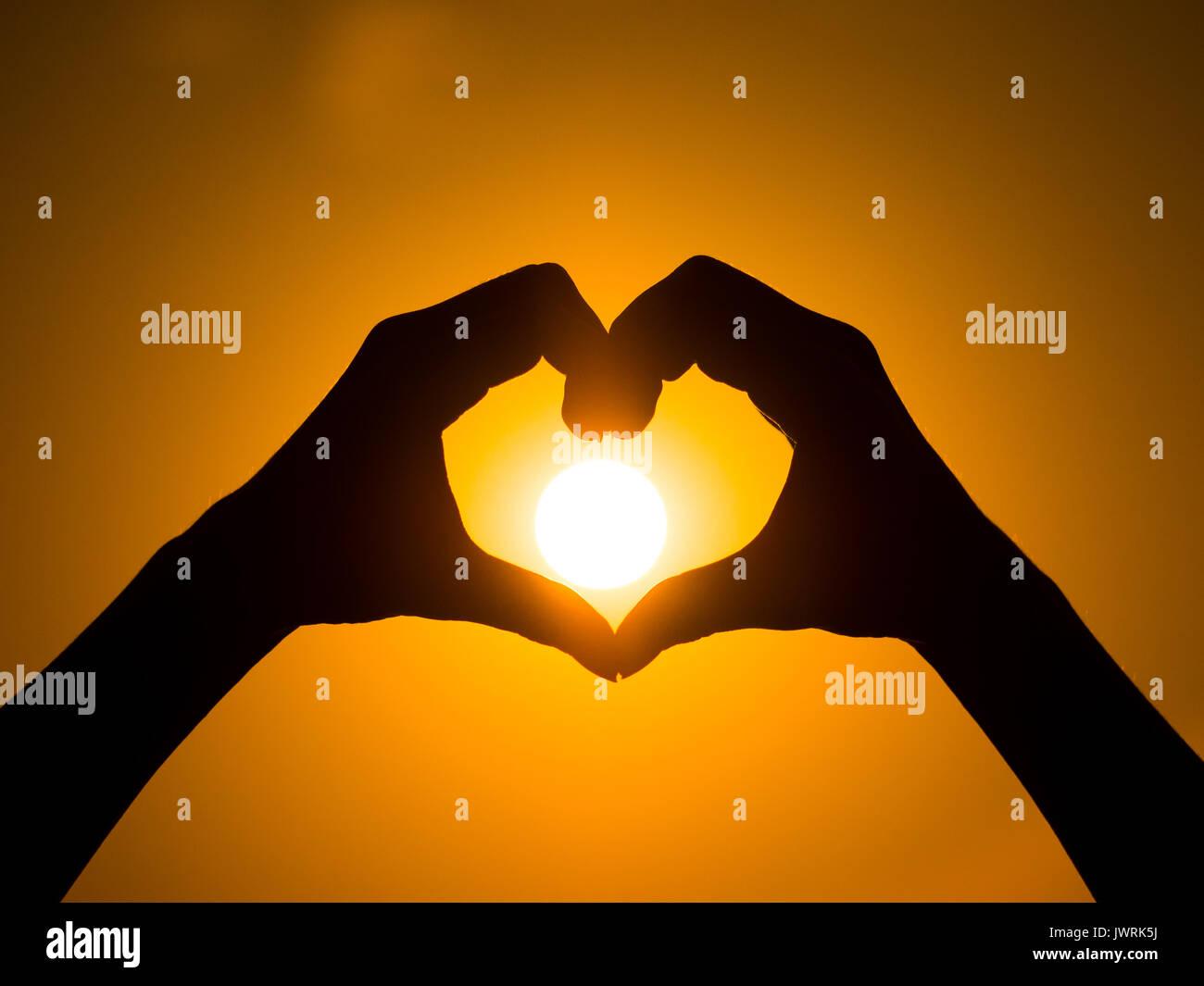 La forma del marco de corazón mano silueta contra el sol y el cielo ...