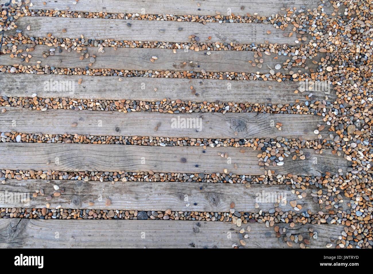 Resbalosa senda hecha de tiras de madera llena de pequeños guijarros. Imagen De Stock