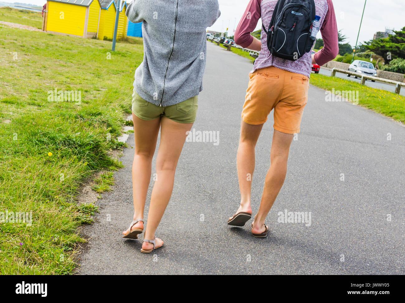 Una joven pareja caminando por el paseo que vistan pantalones cortos, mostrando sólo sus piernas desnudas. Foto de stock