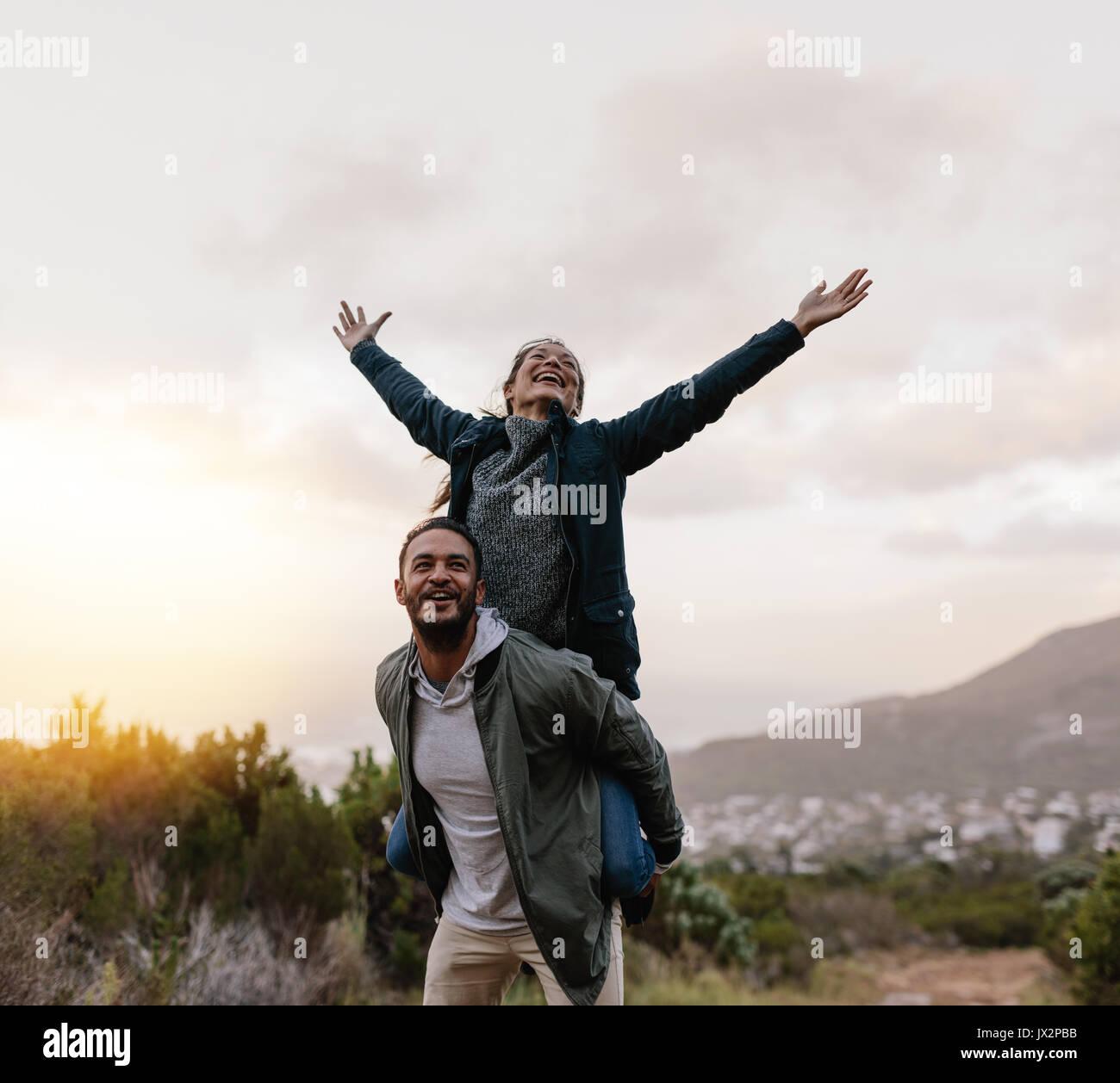 Retrato de joven sumarse a su novia. El hombre lleva la mujer con sus brazos levantados. Pareja disfrutando del paisaje. Imagen De Stock