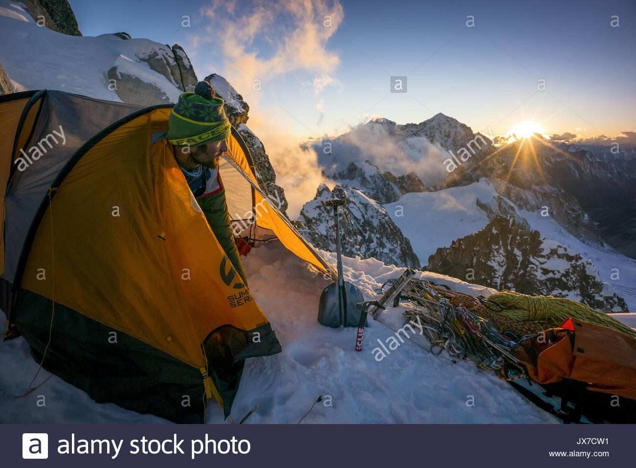 Un montañero surge de una carpa en el Campamento III como el sol se pone con Gamalang Razi en la distancia. Imagen De Stock