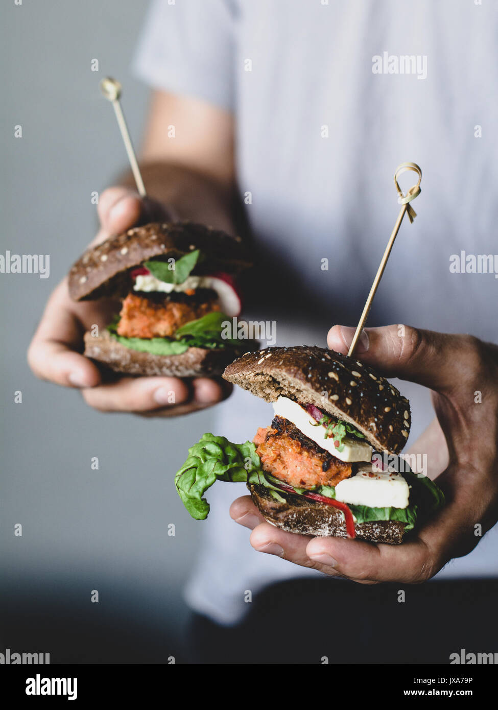 Young hipster celebración vegetariano tofu zanahoria hamburguesas. Closeup view, el enfoque selectivo Imagen De Stock