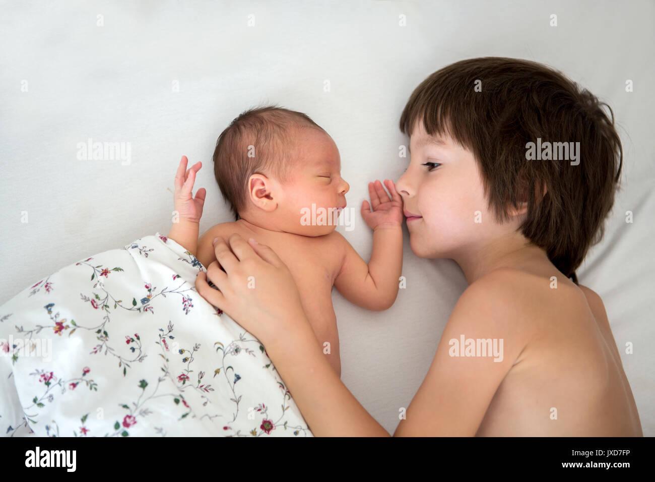 Hermoso muchacho, abrazando con ternura y el cuidado de su bebé recién nacido hermano en casa. Concepto el amor la felicidad de la familia Imagen De Stock