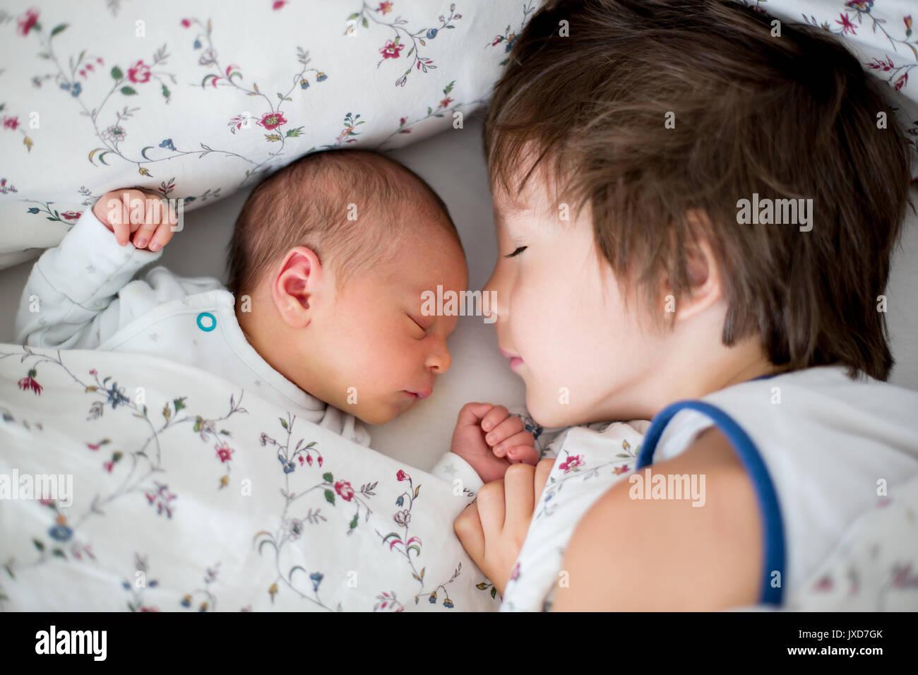 Hermoso muchacho, abrazando con ternura y el cuidado de su bebé recién nacido hermano en casa. Concepto el amor Foto de stock