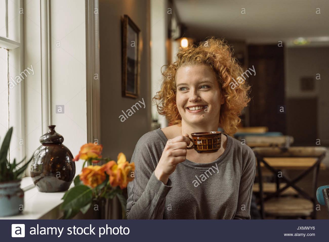 Mujer en el Café Taza holding apartar la mirada sonriendo Imagen De Stock