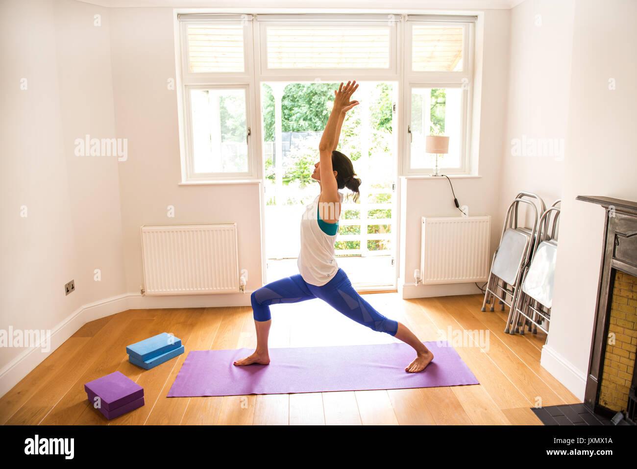 Vista lateral de la mujer los brazos levantados en posición de yoga Imagen De Stock