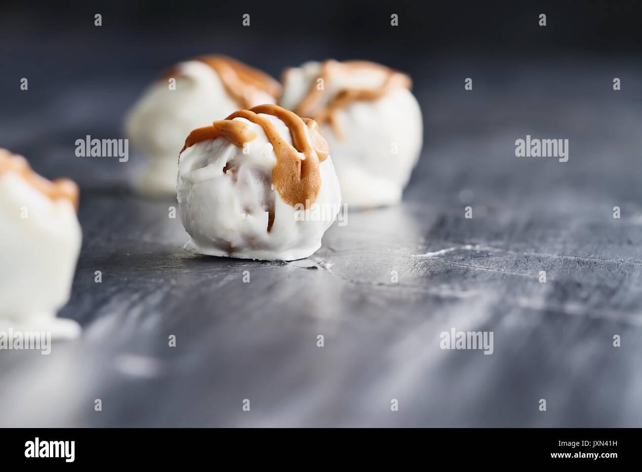 Trufas de chocolate blanco para Navidad o San Valentín aderezada con salsa de mantequilla de maní. Profundidad de campo extremas con el enfoque selectivo en c Foto de stock