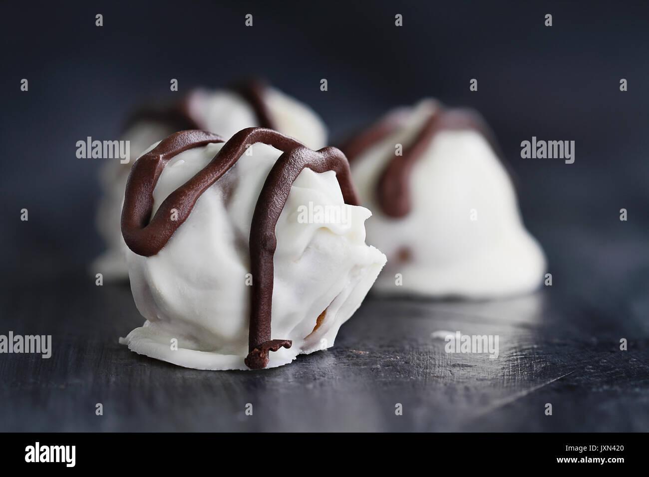 Trufas de chocolate blanco para Navidad o San Valentín rociados con chocolate amargo. Profundidad de campo extremas con el enfoque selectivo en dulces Foto de stock