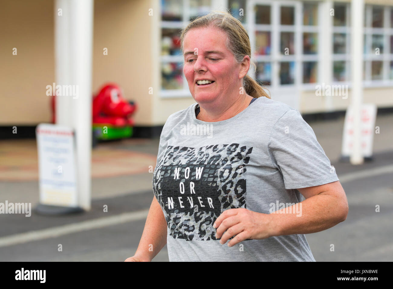 Mujer de mediana edad con sobrepeso ejecutando como parte del plan para perder peso y ponerse en forma, en la vitalidad de Worthing Parkrun evento. Imagen De Stock