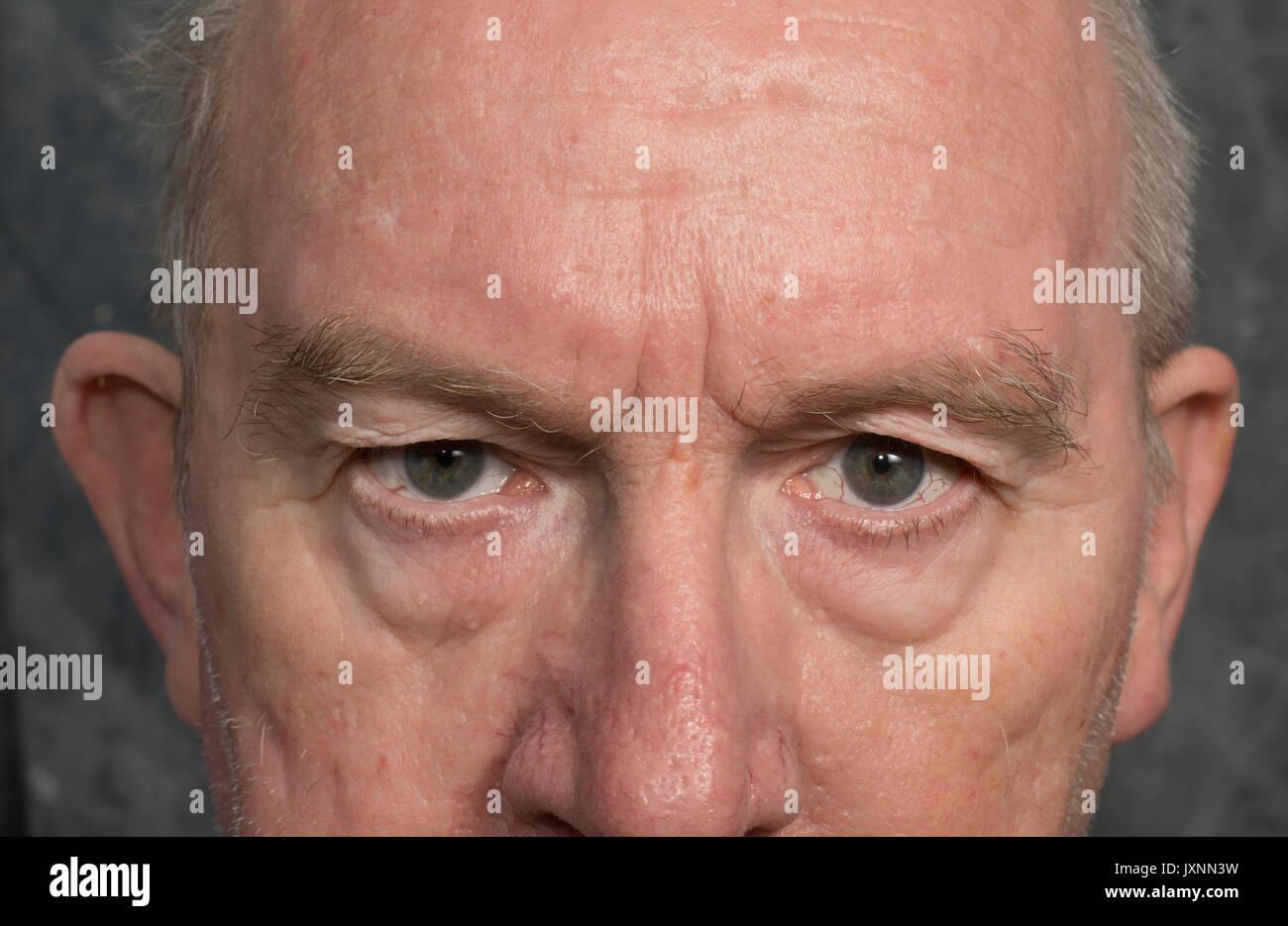 Cerca de los ojos de un hombre mayor de edad, ligeramente hostil. Una hostil, antipático y mirada amenazante Imagen De Stock