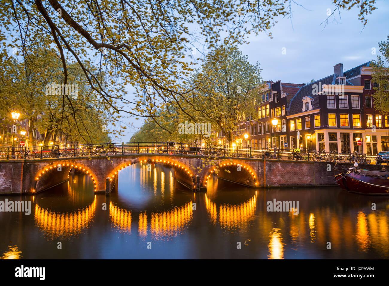 Uno de los famosos canales de Amsterdam, los Países Bajos, al anochecer. Imagen De Stock