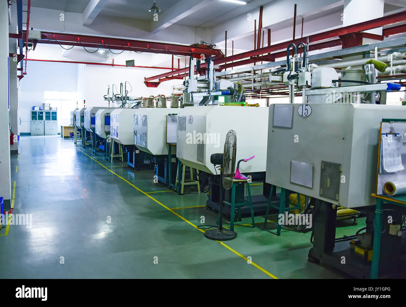 Zona de taller con una fila de máquinas CNC Foto de stock