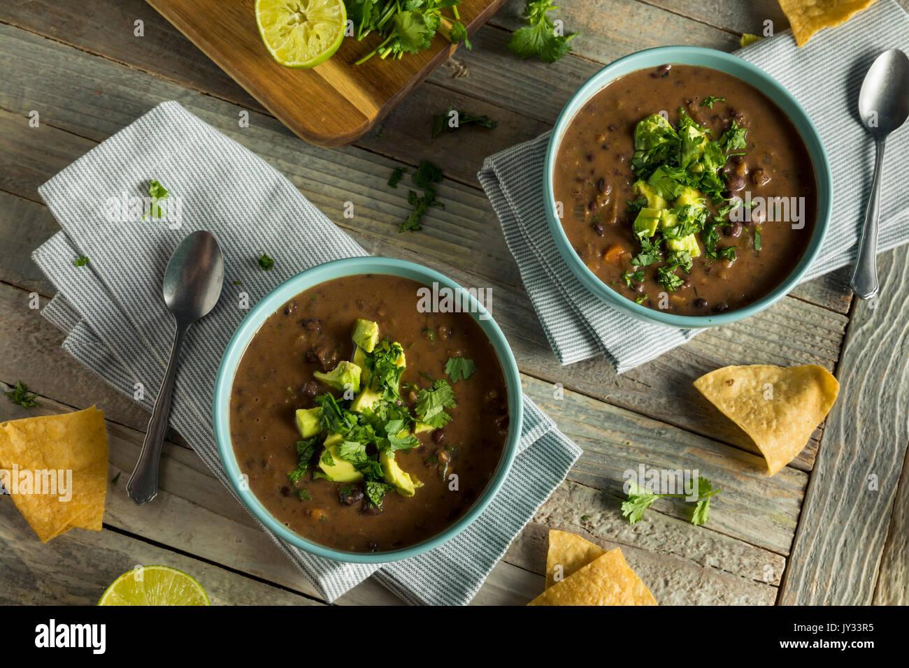 Sopa de Frijoles Negros caseros frescos con aguacate y cilantro. Imagen De Stock