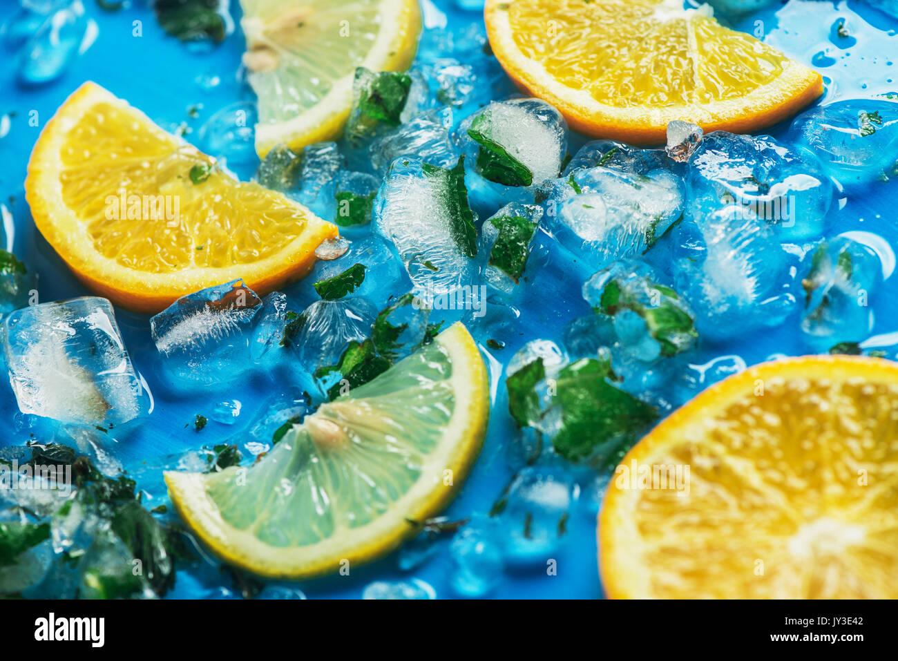 Cerca de rodajas de naranjas y limones en un fondo azul con cubitos de hielo. Imagen De Stock