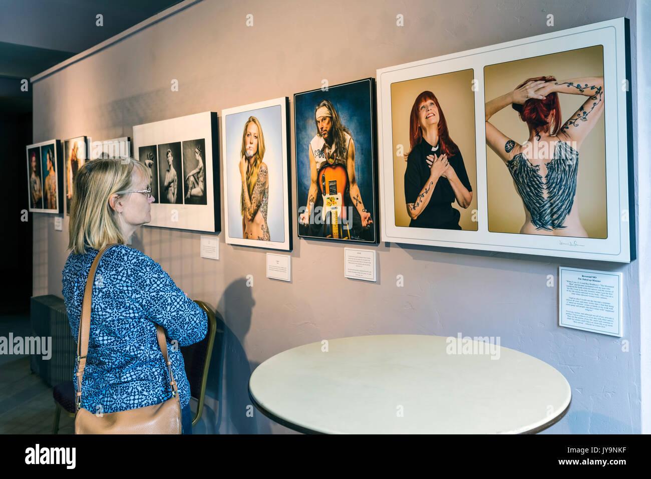 Mujer viendo Gicleé impresiones fotográficas de gente tatuada; Paquette Galería; SteamPlant Event Center; Salida, Colorado, EE.UU. Foto de stock