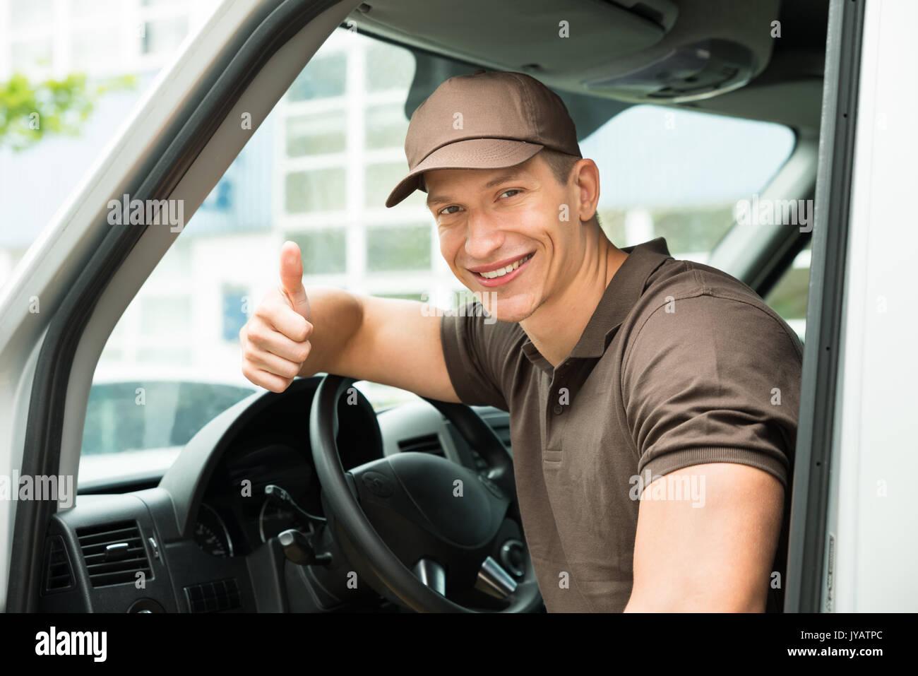 Los jóvenes felices Deliverymen mostrando Pulgar arriba firmar en Van Imagen De Stock